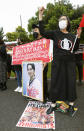 """With a photo of deposed leader Aung San Suu Kyi, Myanmarese residents in Japan and supporters protest against the military takeover, outside the Fukuda Denshi Arena where the Asian qualification soccer match between Myanmar and Japan for the FIFA World Cup Qatar 2022 is held, in Chiba, east of Tokyo, Friday, May 28, 2021. The placard reads """"Myanmar soccer team does not represent the country.""""(Kyodo News via AP)"""