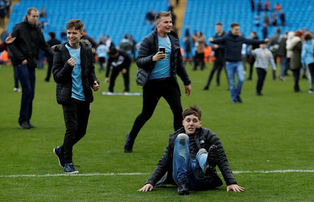"Soccer Football - Premier League - Manchester City v Swansea City - Etihad Stadium, Manchester, Britain - April 22, 2018 Manchester City fans invade the pitch after the game Action Images via Reuters/Lee Smith EDITORIAL USE ONLY. No use with unauthorized audio, video, data, fixture lists, club/league logos or ""live"" services. Online in-match use limited to 75 images, no video emulation. No use in betting, games or single club/league/player publications. Please contact your account representative for further details."