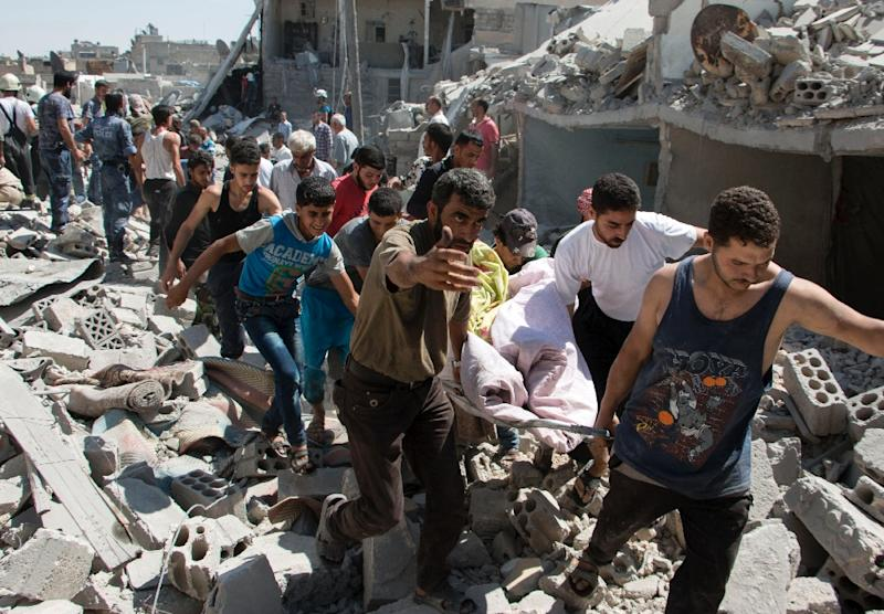 People carry a body on a stretcher over the rubble after a missile fired by Syrian government forces hit a residential area in the Maghayir district of Aleppo on July 21, 2015 (AFP Photo/Karam al-Masri)