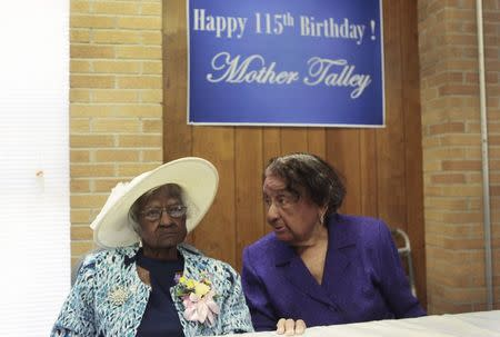 Jeralean Talley (L) sits at the head table with her friend Marian Allen during a celebration of her 115th birthday at the New Jerusalem Missionary Baptist Church in Inkster, Michigan in this file photo taken May 25, 2014. REUTERS/Rebecca Cook