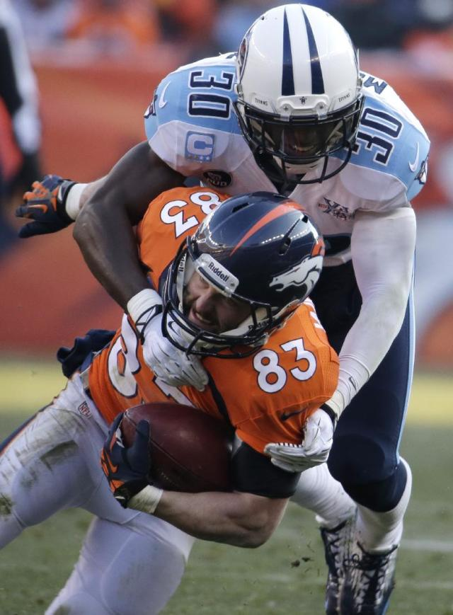 Denver Broncos wide receiver Wes Welker (83) is tackled by Tennessee Titans cornerback Jason McCourty (30) during the first half of an NFL football game on Sunday, Dec. 8, 2013, in Denver. (AP Photo/Jack Dempsey)