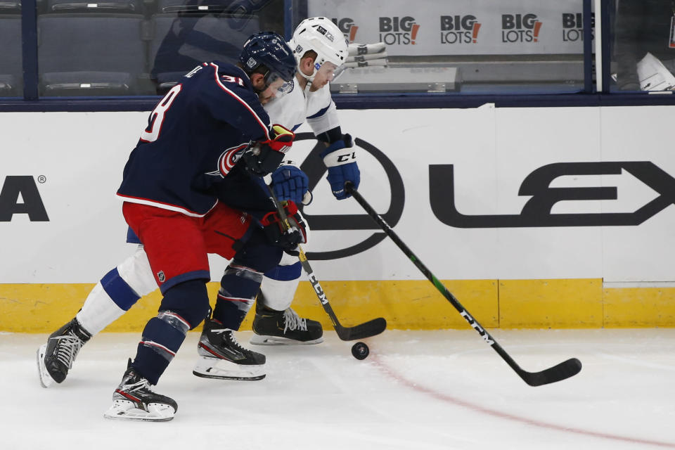 Columbus Blue Jackets' Boone Jenner, left, and Tampa Bay Lightning's Erik Cernak chase the puck during the second period of an NHL hockey game Thursday, Jan. 21, 2021, in Columbus, Ohio. (AP Photo/Jay LaPrete)