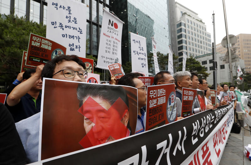 """South Korean small and medium-sized business owners stage a rally calling for a boycott of Japanese products in front of the Japanese embassy in Seoul, South Korea, Monday, July 15, 2019. South Korea and Japan last Friday, July 12, failed to immediately resolve their dispute over Japanese export restrictions that could hurt South Korean technology companies, as Seoul called for an investigation by the United Nations or another international body. The signs read: """"We don't sell Japanese products."""" (AP Photo/Ahn Young-joon)"""