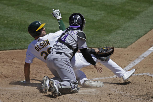 Colorado Rockies catcher Tony Wolters (14) tags out Oakland Athletics' Matt Olson, left, during the fourth inning of a baseball game Wednesday, July 29, 2020, in Oakland, Calif. (AP Photo/Ben Margot)