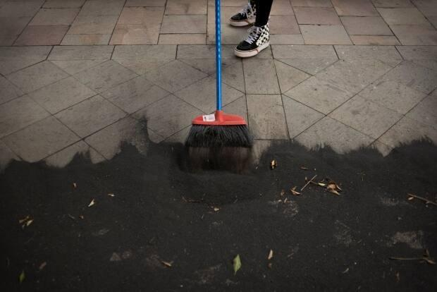 A woman cleans an ash-covered street with a broom on the Canary Island of La Palma on Sunday as a volcano on the island continues to erupt. (Jorge Guerrero/AFP via Getty Images - image credit)