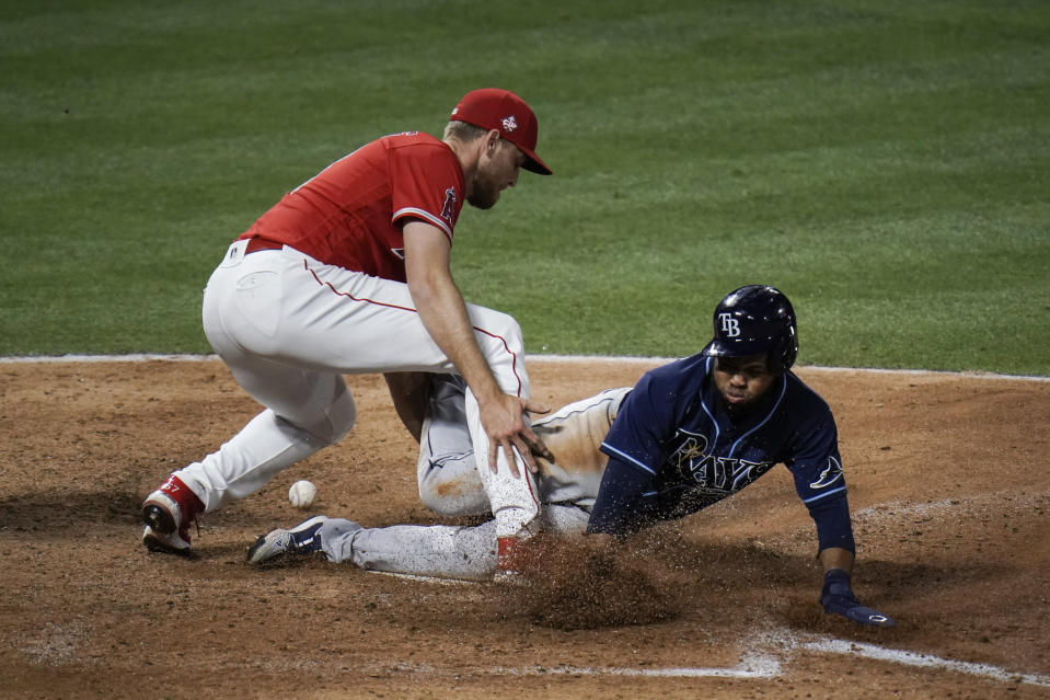 Tampa Bay Rays' Manuel Margot, right, scores as Los Angeles Angels relief pitcher Aaron Slegers misses the throw during the eighth inning of a baseball game Thursday, May 6, 2021, in Anaheim, Calif. (AP Photo/Jae C. Hong)