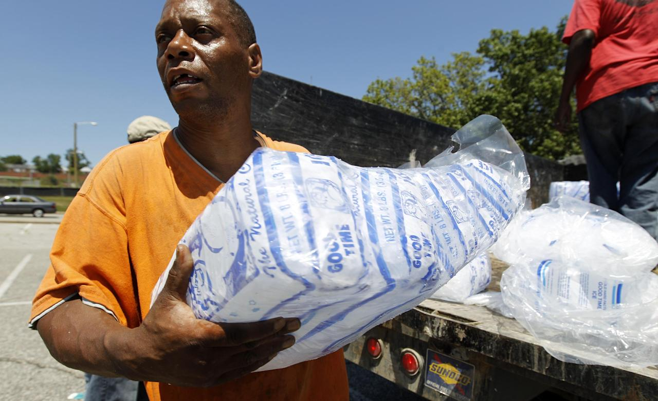 Baltimore city worker Joe Lane give away free bags of ice to residents at the Northwood Plaza shopping center, in Baltimore on Monday, July 2, 2012. Around 2 million customers from North Carolina to New Jersey and as far west as Illinois were without power Monday morning after a round of summer storms. (AP Photo/Jose Luis Magana)