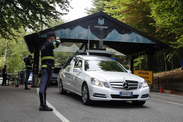 A police officer salutes as a hearse passes by, on the road leading to the Stresa-Mottarone after a cable car of the line collapsed, near Stresa, Italy, Sunday, May 23, 2021. A cable car taking visitors to a mountaintop view of some of northern Italy's most picturesque lakes plummeted to the ground Sunday and then tumbled down the slope, killing at least 13 people and sending two children to the hospital, authorities said. (AP Photo/Antonio Calanni)