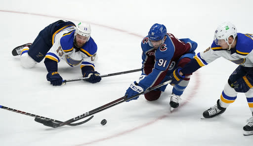 Colorado Avalanche center Nazem Kadri, centyer, fights for control of the puck with St. Louis Blues left wing Kyle Clifford, left, and center Ivan Barbashev in the first period of an NHL hockey game Friday, Jan. 15, 2021, in Denver. (AP Photo/David Zalubowski)