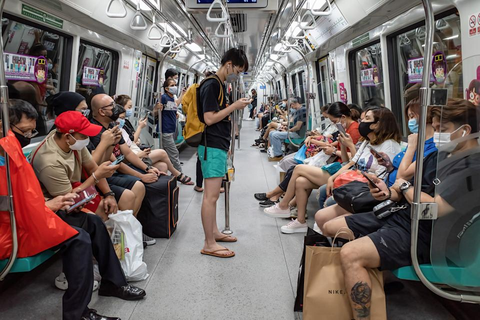 SINGAPORE - 2021/05/22: People wearing face masks as a preventive measure against the spread of covid19 are seen on a train in Singapore. Singapore has tightened its Covid-19 restrictions from May 16 to June 13 due to the rise of Covid-19 cases in the community. During this time, only groups of 2 people outside will be allowed, malls and attractions are to reduce capacity, and dining-in at eateries are prohibited. (Photo by Maverick Asio/SOPA Images/LightRocket via Getty Images)