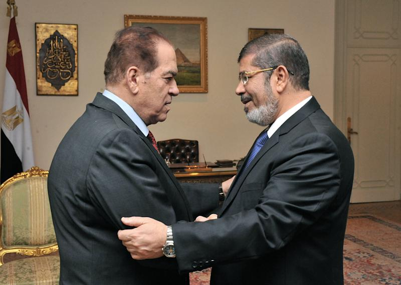 In this photo released by Middle East News Agency, the Egyptian official news agency, caretaker Prime Minister Kamal el-Ganzouri, left, shakes hands with newly elected President Mohammed Morsi in Cairo, Egypt, Monday, June 25, 2012. Morsi met with the military-backed Prime Minister el-Ganzouri, who resigned Monday and was asked to head a caretaker government until Morsi nominates a new one. The election of an Islamist president in Egypt is turning longstanding U.S. policy in the Mideast inside out. The Obama administration is relieved that the candidate who represents three decades of close partnership with the United States was beaten by an Islamic fundamentalist. (AP Photo/Middle East News Agency, HO)