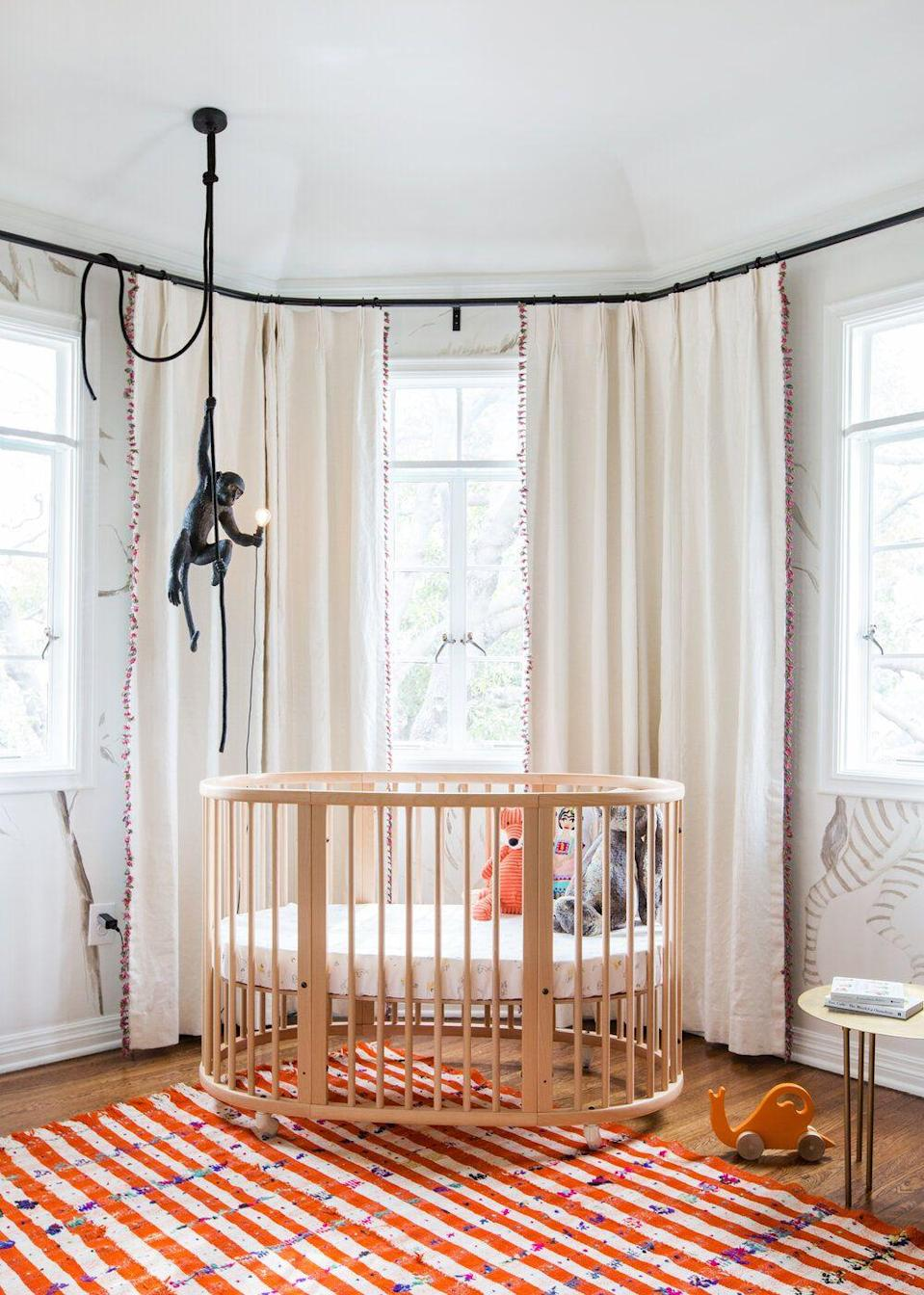 """<p>Orange is such an underrated nursery color. In this one designed by <a href=""""https://www.etcforshort.com/"""" rel=""""nofollow noopener"""" target=""""_blank"""" data-ylk=""""slk:ETC.era"""" class=""""link rapid-noclick-resp"""">ETC.era</a>, the bold rug sets the tone for an energizing, fun, and sweet space. Keep things soft and cozy with a warm cream as opposed to a cool white. And how could we not mention that awesome monkey pendant? </p>"""