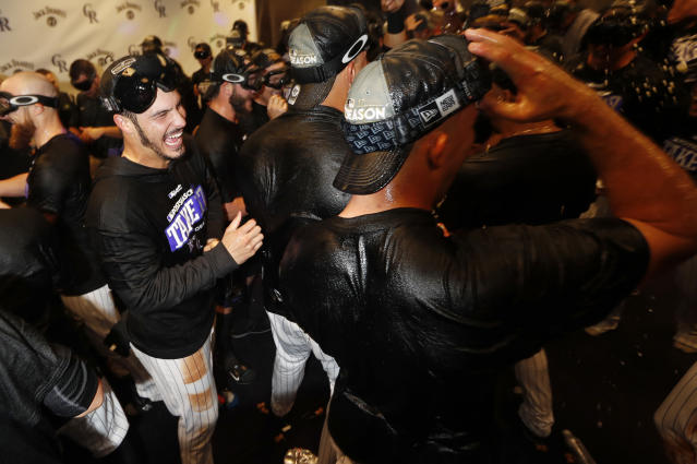 Rockies third baseman Nolan Arenado (left) celebrates with teammates after securing a National League Wild Card berth on Saturday. (AP)