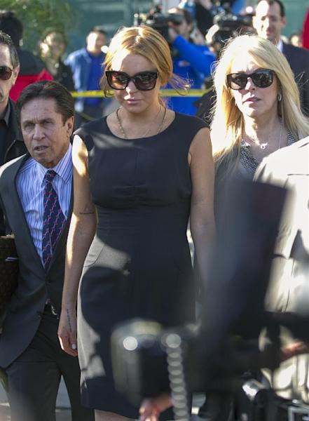 Lindsay Lohan, center, her mother Dina Lohan, right, her new attorney Mark Heller leave a Los Angeles court, Wednesday, Jan. 30, 2013, in a case filed over the actress' car crash last June. A judge has delayed Lohan's trial on three misdemeanor counts. She pleaded not guilty to lying to police, reckless driving and obstructing officers from performing their duties. (AP Photo/Damian Dovarganes)