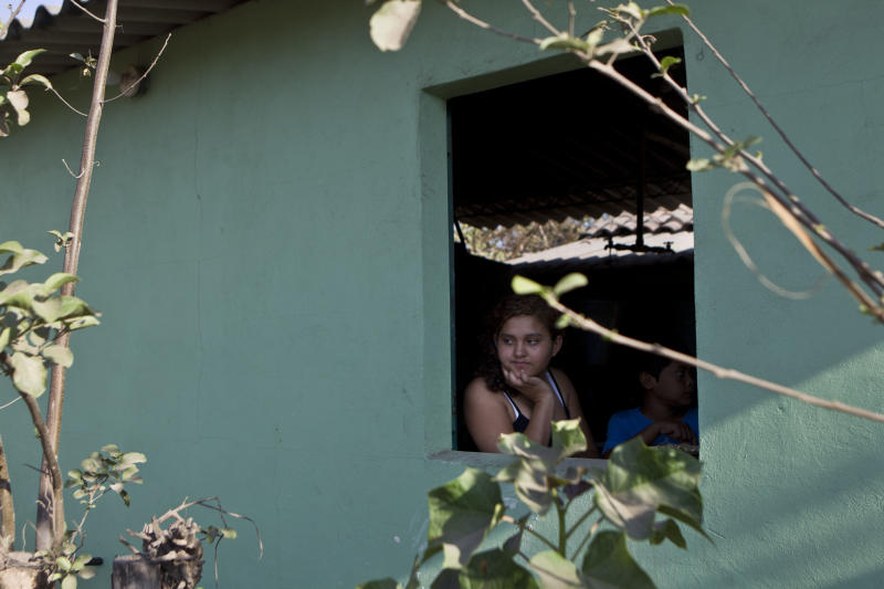 Fatima Alvarenga, daughter of Jose Salvador Alvarenga, looks out the window of her family's home in the village Garita Palmera, El Salvador, Tuesday, Feb. 4, 2014. The account of her father's survival after more than 13 months in an open boat has proven a double miracle for his family, who lost touch with him years ago and thought he was dead. Alvarenga says he left Mexico early 2012 for a day of shark fishing and ended up on the remote Marshall Islands. (AP Photo/Esteban Felix)