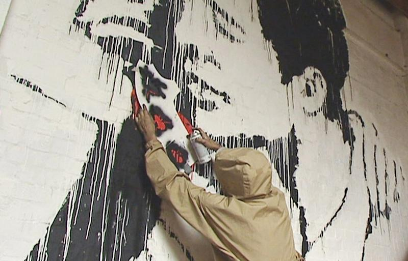 'Banksy' adds extra touches to his 'Turf War' exhibition during the archived news footage.