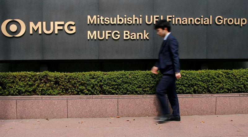 FILE PHOTO: A man walks past a signboard of Mitsubishi UFJ Financial Group at its headquarters in Tokyo