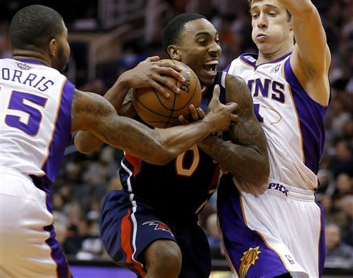 Atlanta Hawks' Jeff Teague (0) tries to drive past Phoenix Suns' Markieff Morris, left, and Goran Dragic, of Slovenia, during the first half of an NBA basketball game, Friday, March 1, 2013, in Phoenix. (AP Photo/Matt York)