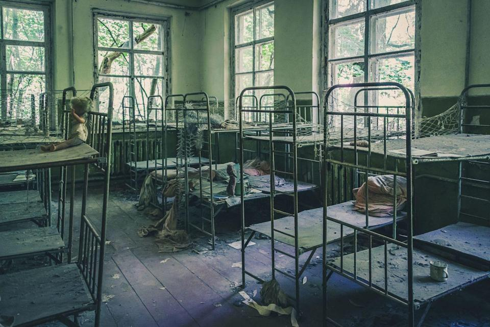 <p>Rows of empty bunk beds line the walls of this abandoned mental facility.</p>