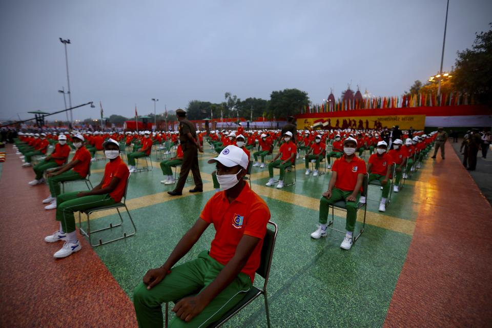 People wearing face masks and dressed in the colors of the national flag wait for the start of the Independence Day ceremony on the ramparts of the landmark Red fort monument in New Delhi, India, Saturday, Aug. 15, 2020. India's coronavirus death toll overtook Britain's to become the fourth-highest in the world with another single-day record increase in cases Friday. (AP Photo/Manish Swarup)