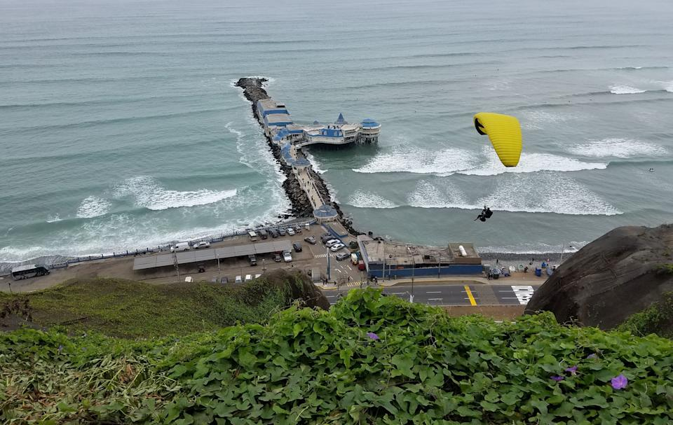 A paraglider is seen from the cliffs overlooking the Pacific Ocean in Lima's upscale neighbourhood of Miraflores, on August 20, 2016. / AFP / Daniel SLIM        (Photo credit should read DANIEL SLIM/AFP/Getty Images)