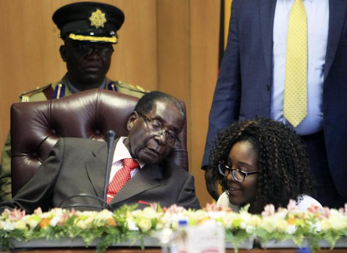"""Zimbabwe's President Robert Mugabe talks to his daughter Bona as he marks his 93rd birthday at his offices in Harare, Tuesday, Feb. 21, 2017. Mugabe described his wife Grace, an increasingly political figure, as """"fireworks"""" in an interview marking his 93rd birthday. (AP Photo/Tsvangirayi Mukwazhi)"""
