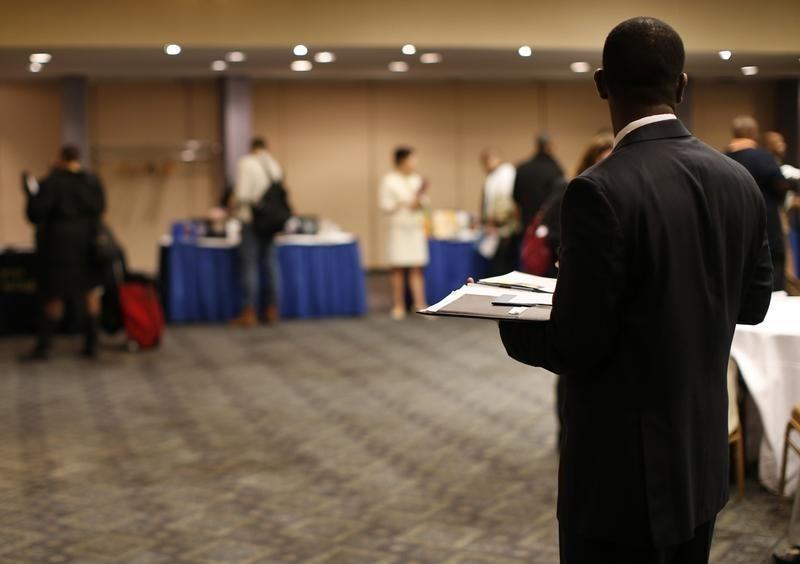 A job seeker stands in a room of prospective employers at a career fair in New York City
