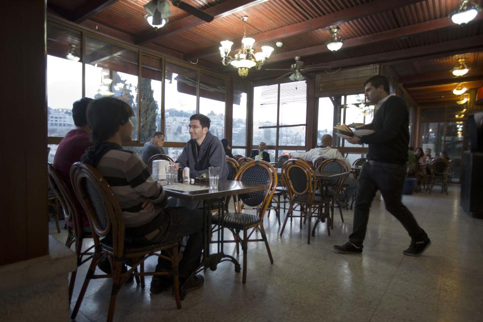 Diners sit in a restaurant in the village of Abu Ghosh, on the outskirts of Jerusalem, Wednesday, Nov. 20, 2013. A restaurant owner in an Arab village outside of Jerusalem says he is on a mission to save culinary culture by making diners a simple offer: Turn off your cellphone and get a 50 percent discount. (AP Photo/Sebastian Scheiner)