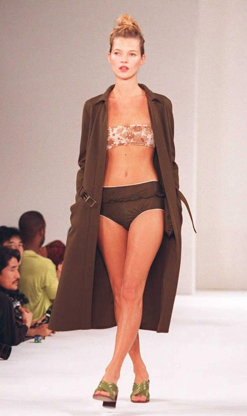 Supermodel Kate Moss wears a brown swimsuit with a flowered top and a long coat during the Miu Miu Spring/Summer 1996 fashion show 02 November in New York.
