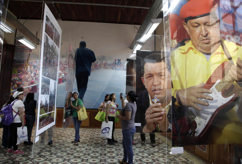 In this March 20, 2013 file photo, people visit the Military Museum where photos of the late President Hugo Chavez are exhibited near his tomb in Caracas, Venezuela. The late leader transformed this country's enormous federal bureaucracy into nothing less than a political arm of the government, say former government workers and experts, with partisan loyalties trumping technical competence in hiring and ministries turning out thousands of civil servants for election year rallies. (AP Photo/Ariana Cubillos, File)