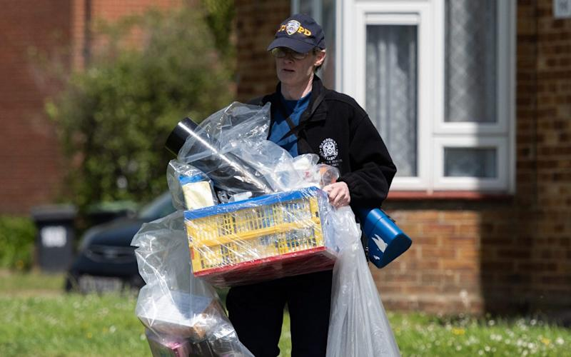 A police officer carries out bagged items from a property in Havant where Louise Smith was staying before she vanished on May 8   - Jordan Pettitt/Solent