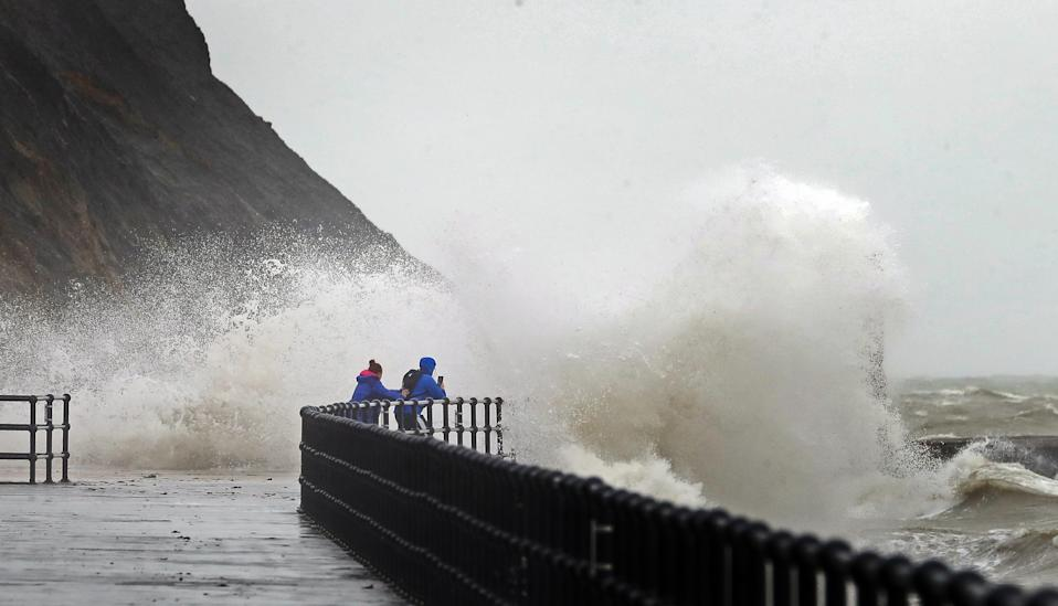People take pictures of the waves hitting the harbour wall in Folkestone, Kent. Parts of the UK are preparing to be lashed by heavy rain and high winds as Storm Alex heralds the arrival of a stretch of bad weather over the weekend.