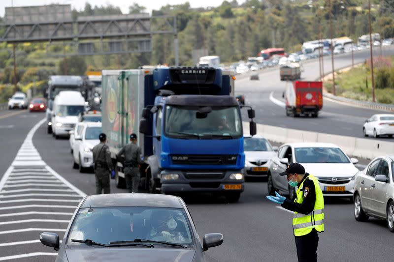 A driver speaks to a policeman at a roadblock as police begin to enforce a national lockdown to fight the spread of the coronavirus disease (COVID-19) on a road leading to Jerusalem, near Ein Hemed