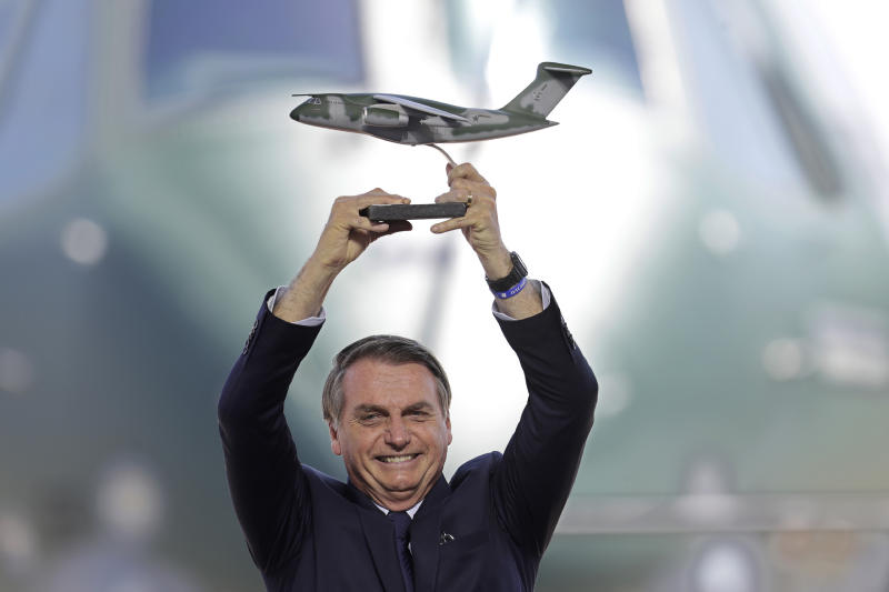 Brazil's President Jair Bolsonaro holds up a miniature of a KC-390 plane during the Brazilian Air Force delivery ceremony of the first military aircraft KC-390, at the air base in Anapolis, Brazil, Wednesday, Sept. 4, 2019. The aircraft is capable of transporting and launching cargo and troops, as well as a wide range of missions: air evacuation, search and rescue, firefighting, air refueling and humanitarian aid. (AP Photo/Eraldo Peres)