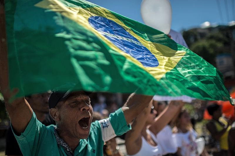 """People participate in a """"march for peace"""" at Rio de Janeiro's Alemao favela on April 4, 2015 (AFP Photo/Christophe Simon)"""