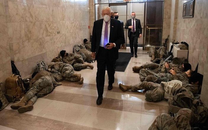 House Majority Leader Steny Hoyer, Democrat of Maryland, walks past members of the National Guard as he arrives at the US Capitol - Saul Loeb/AFP