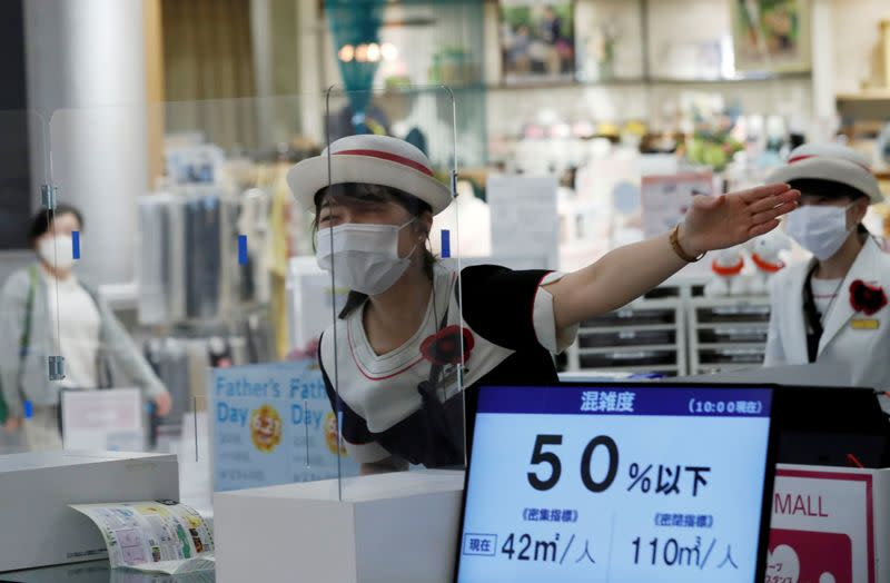 FILE PHOTO: A staff at an information desk talks to a customer through a transparent plastic panel at Japan's supermarket group Aeon's shopping mall as the mall reopens amid the coronavirus disease (COVID-19) outbreak in Chiba