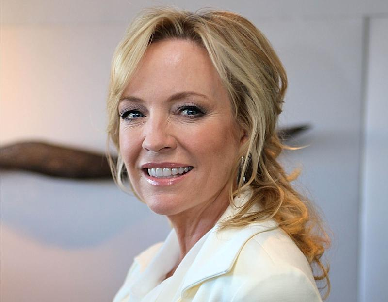 Australian actress Rebecca Gibney poses in white suit and ponytail