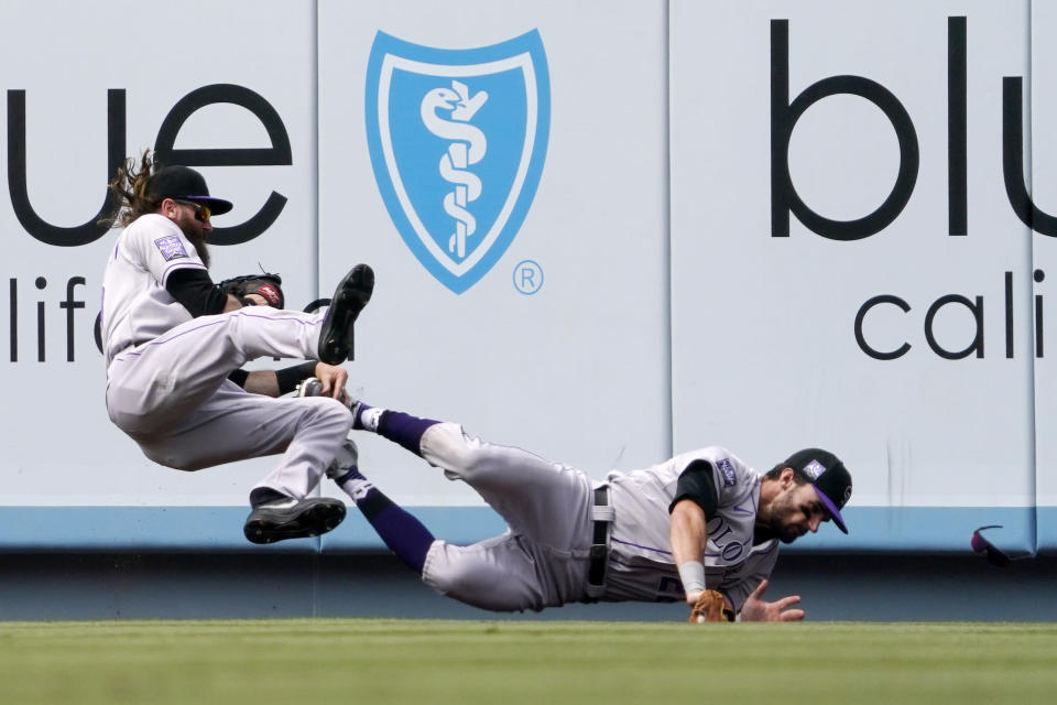 Colorado Rockies right fielder Charlie Blackmon, left, falls after making a catch on a ball hit by Los Angeles Dodgers' Zach McKinstry and colliding with center fielder Sam Hilliard during the sixth inning of a baseball game Sunday, July 25, 2021, in Los Angeles. (AP Photo/Mark J. Terrill)