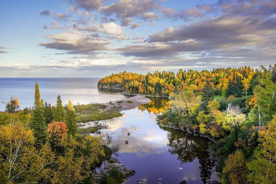 """<p>From the jawdropping views of Lake Superior to the endless sea of maple trees, the North Shore of Minnesota is cited as having two peak seasons in mid-September and mid-October. There are countless serene small towns, natural landmarks, and vast trails to be seen along the 145-mile stretch. One of our favorite stops, Grand Marais has the perfect blend of in-town attractions like eclectic shops and galleries and adventurous activities like kayaking and fishing. </p><p><em>Where to Stay: <a href=""""https://www.bluefinbay.com/"""" rel=""""nofollow noopener"""" target=""""_blank"""" data-ylk=""""slk:Bluefin Bay"""" class=""""link rapid-noclick-resp"""">Bluefin Bay</a> in Grand Marais, Minnesota</em></p>"""