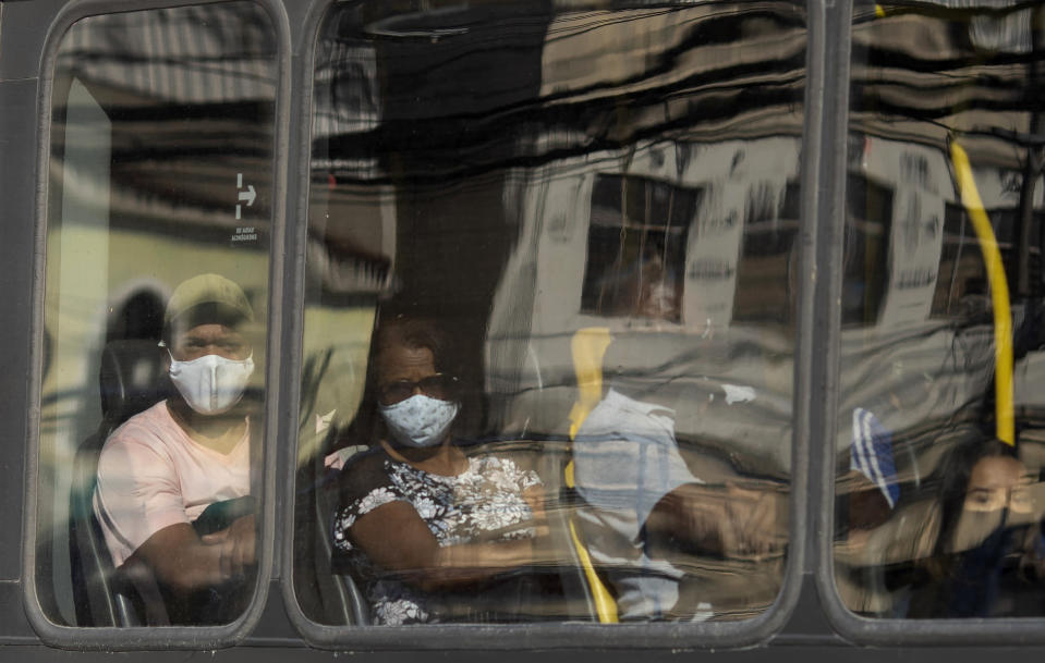 Commuters wearing face masks peer through a bus window during increased restrictions on movements in an effort to curb the spread of the new coronavirus in the Madureira area of Rio de Janeiro, Brazil, Tuesday, May 12, 2020. (AP Photo/Silvia Izquierdo)