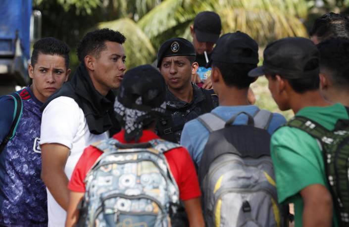 A Guatemalan police officer stops Honduran migrants trying to reach the United States who crossed the Honduran border, in Morales, Guatemala, Wednesday, Jan. 15, 2020. Migrants in the group said they left Honduras very late Tuesday, around midnight. (AP Photo/Moises Castillo)