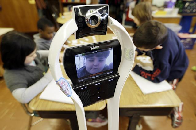 In this Thursday, Jan. 24, 2013 photo, Devon Carrow attends Winchester Elementary School from home while operating a robot in the classroom, in West Seneca N.Y. Carrow's life-threatening allergies don't allow him to go to school. But the 4-foot-tall robot with a wireless video hookup gives him the school experience remotely, allowing him to participate in class, stroll through the hallways, hang out at recess and even take to the auditorium stage when there's a show. (AP Photo/David Duprey)