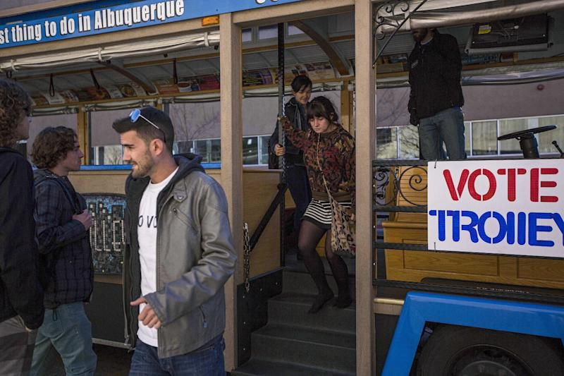 """University of New Mexico students exit the """"Voting Trolly"""" at a stop on campus in Albuquerque, N.M., on Tuesday, Nov. 14, 2013. ABQ Trolley Co. partnered up with the non-profit Progress Now New Mexico to provide University of New Mexico students transportation to voting sites due to a prior vote by the Albuquerque City Council that excluded the university as a voting site for a special ballot. Albuquerque voters will decide whether to ban abortions after 20 weeks following an emotional and graphic campaign that has included protests and hundreds of thousands of dollars on television and radio ads that have brought out more than twice as many early voters as the recent mayoral elections. (AP Photo/Juan Antonio Labreche)"""