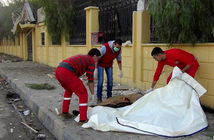 Rescue workers remove a body following air strikes reportedly by Syrian government forces in the Islamic State (IS) group controlled Syrian city of Raqa, on November 25, 2014 (AFP Photo/-)