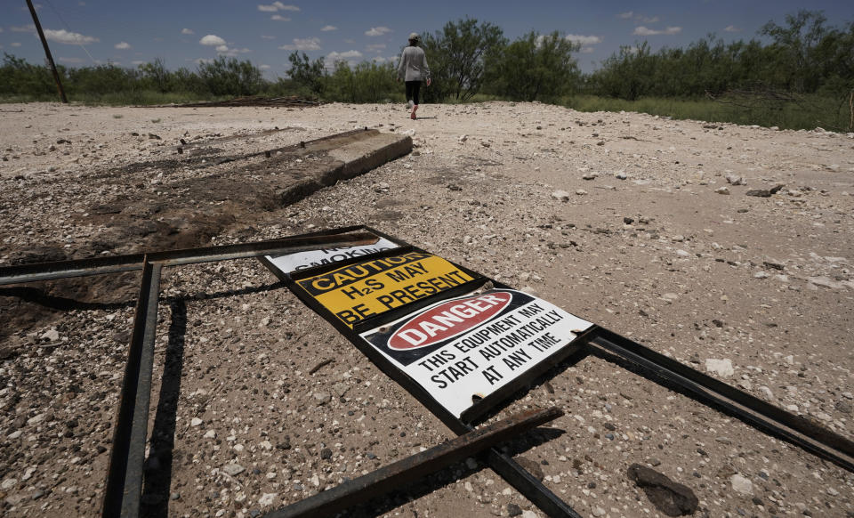 Ashley Williams Watt walks across the site of an abandoned well at her ranch, Friday, July 9, 2021, near Crane, Texas. Some of her wells are leaking chemicals such as benzene, a known carcinogen, into fields and drinking water. (AP Photo/Eric Gay)