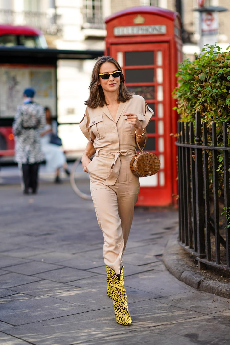 Therese Hellstrom is seen wearing a cream jumpsuit, accessorised with a brown crocodile print bag and statement yellow leopard print western boots. [Photo: Getty Images]