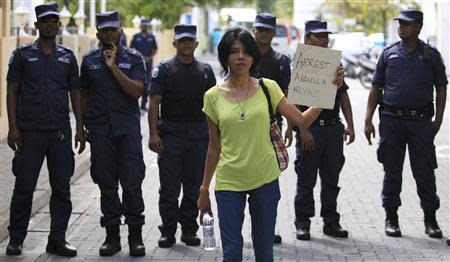 Supporter of presidential candidate Nasheed, who was ousted as president in 2012, holds up a placard during a protest against the Maldives police, in Male