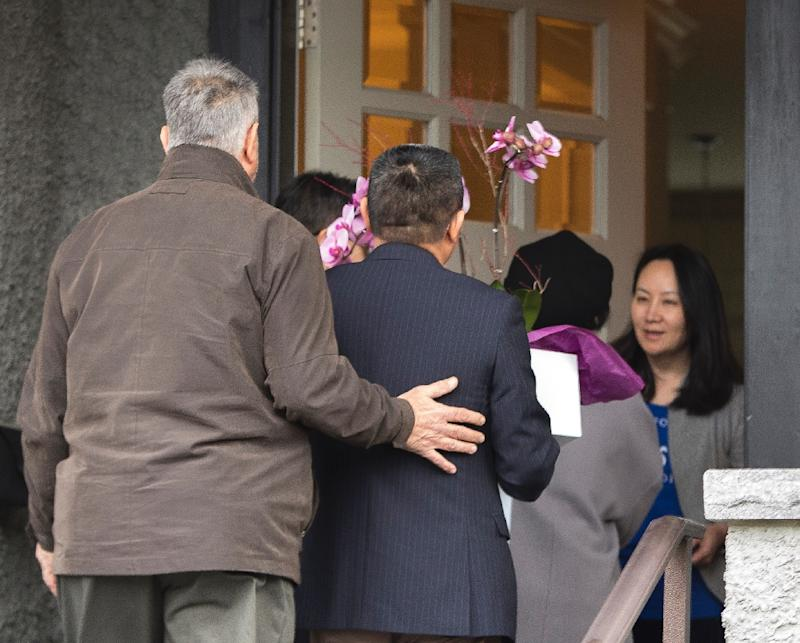 Meng Wanzhou (R), Chief Financial Officer of Huawei Technologies, answers the door on December 12, 2018 after she was released on bail  in Vancouver, British Columbia