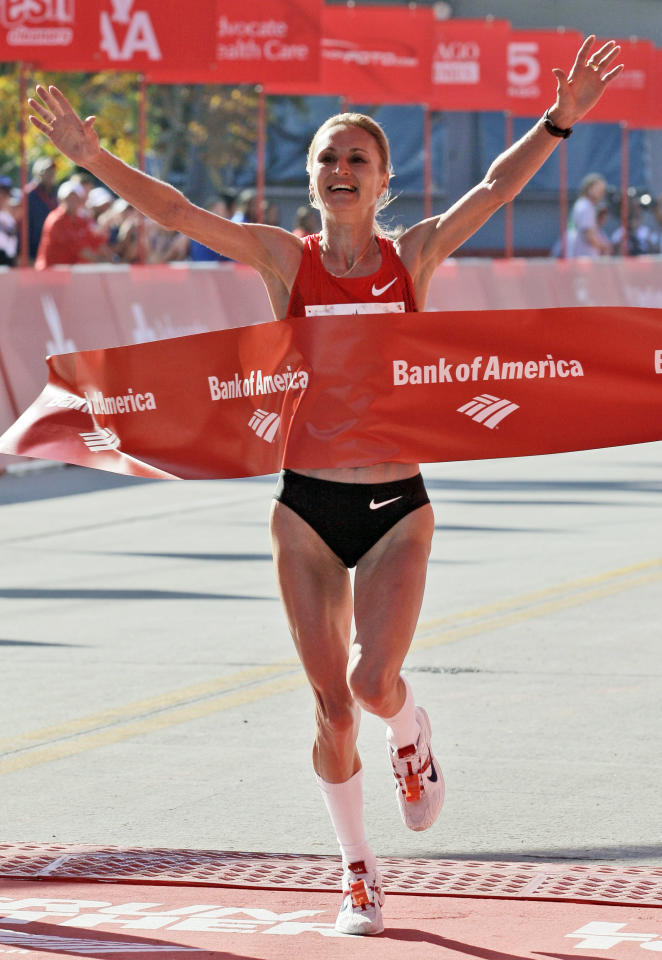 FILE - In this Oct. 9, 2011, file photo, Lilya Shobukhova, of Russia, celebrates as she crosses the finish line to win the women's division of the Chicago Marathon in Chicago. The three-time Chicago Marathon winner has been banned for two years for blood doping. The Russian athletics federation says it banned Shobukhova until next January and stripped her results from Oct. 9, 2009, for abnormal biological passport values. (AP Photo/Nam Y. Huh, File)